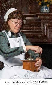 """Vintage scene of a victorian woman working with a coffee grinder. Shot in the antique castle """"Den Brandt"""" in Antwerp, Belgium (with signed property release for the Castle interiors)."""