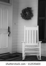Vintage scene of white rocking chair on front porch next to front door
