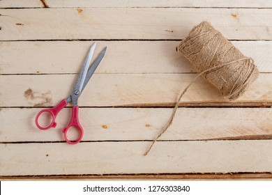 Vintage scissors on a wooden background with twine and convoy. Top view with place for text.