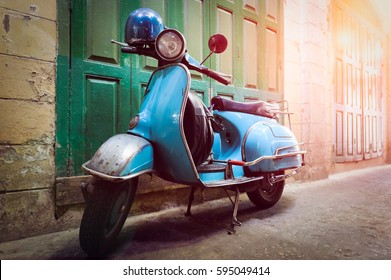 Vintage scooter stands in an alley. Post process in vintage styl