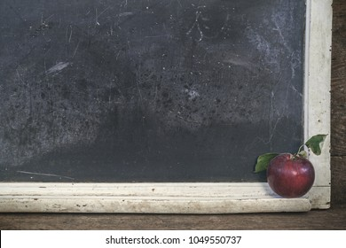 Vintage Scratched chalboard on a vintage table with apple