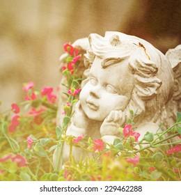 vintage sculpture of little angel among flowers