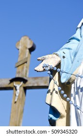 vintage sculpture of St. Mary hand and blur cross