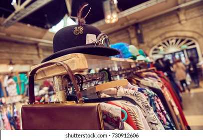 Vintage second hand hat and clothes rail showing colourful vintage clothes on coat hangers.