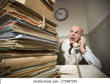 Vintage senior businessman on the phone with a huge stack of files.