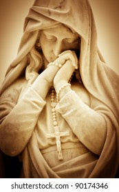 Vintage sepia image of a suffering religious woman with a crucifix