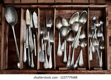 A Vintage service cutlery inside a rustic wooden box.