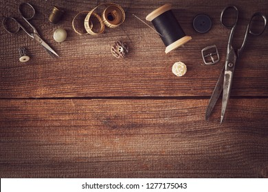 vintage sewing things with scissors, yarn,buttons,thimble and measuring tape flat lay on wooden board with copy space
