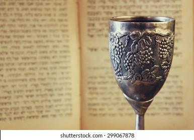 vintage shabbath kiddush cup of wine in front of blurred torah prayer book