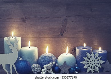 Vintage, Shabby Chic Chirstmas Decoration With Purple And Blue Candles,Reindeer, Christmas Ball, Snowflake, Fir Cone,Star. Peaceful Atmosphere With Candlelight. Wooden Background For Copy Space