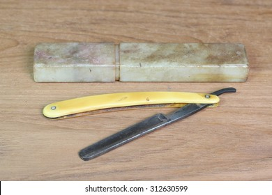 Vintage shaving blade isolated On a wooden background.