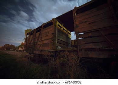 Vintage sheep train carriages under a cloudy, full moon.