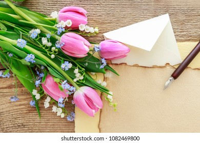 Vintage sheets of paper, pen, bouquet of pink tulips, lily of the valley and forget me not flowers.