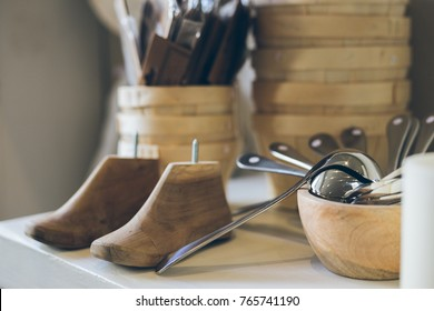 Vintage shoe lasts, kitchen tools and wooden bowls and baskets in a homeware boutique.