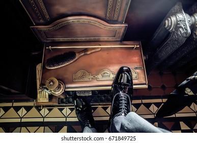 Vintage shoe shine machine and elegant gentleman black leather shoes