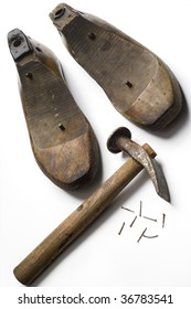 vintage shoemaker's tools - hammer and shoes molds - on white