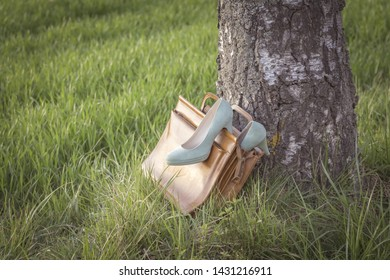Vintage shoes pumps wayside in nature arouse wanderlust in bag. Symbol for passion adventures spontaneity and desire for silence and resting. Sabbatical break from daily stress brings fresh restart