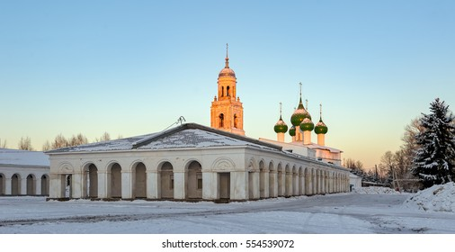 Vintage shopping arcade on the Marketplace and Holy Trinity Cathedral Church in Poshekhonie small town, Yaroslavl region, Russia at early winter morning