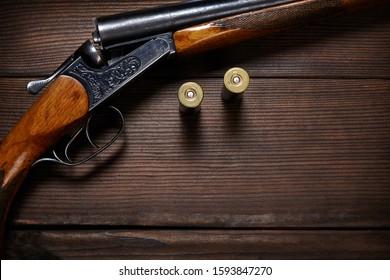Vintage shotgun and ammunition on a wooden background.