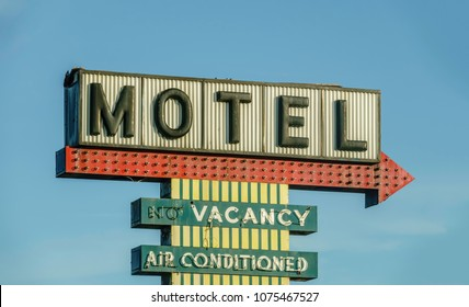 Vintage sign above motel parking lot on a sunny evening, for themes of travel, lodging, Americana