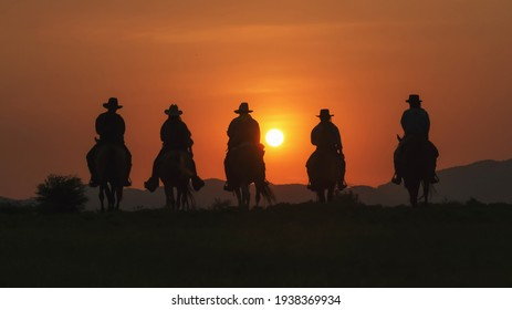 Vintage and silhouettes of a group of cowboys sitting on horseback at sunset.
