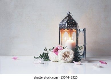 Vintage silver Moroccan, Arabic lantern with glowing candle, green branches, rose flowers and pink petals on white table background. Greeting card for Muslim holiday Ramadan Kareem. Shaby wall.
