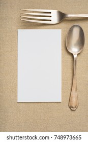 Vintage Silverware Setting of fork and spoon on Holiday Gold Lame' Table Place mat with an empty white menu or name card with room or space for your words, design, text or copy. A Vertical flat lay