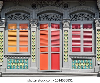 Vintage Singapore Straits Chinese or Peranakan shop house with antique orange and red wooden shutters, arched windows and ornamental Chinese tiles.