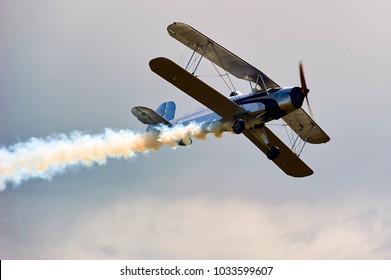 Vintage single engine propeller biplane aircraft flying at sunset