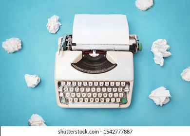 Vintage Sixties typewriter with wadded paper balls on a teal background