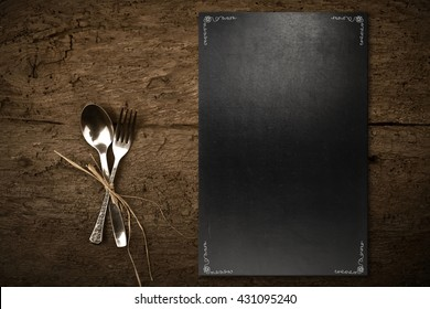 Vintage slate chalkboard template menu and spoon and fork on dark wooden background