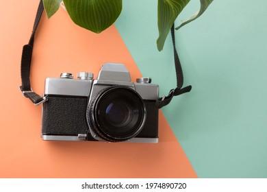 Vintage SLR Camera On Coloured Background Orange Green with green plant Prime Lens Film Camera Metal