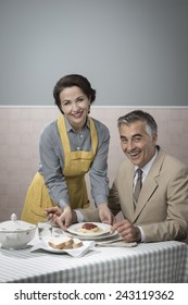 Vintage smiling woman serving pasta for lunch to her happy husband