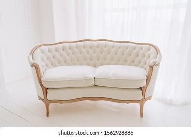 Vintage-Sofa auf Holzfußboden Weiß Design. Komfortable Retro Couch mit Cushions Dekoration Nahaufnahme. Elegantes Divan-Bett Classic Style New Residence Zimmer Modernes Apartment Hintergrund