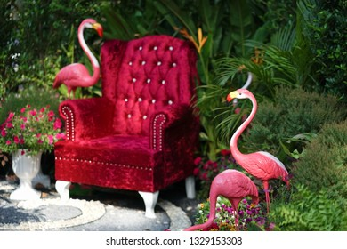 Vintage sofa. A red velvet vintage armchair in the garden with pink flamingo. soft focus on the pink flamingo