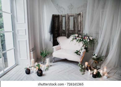 vintage sofa of soft pink color, decorated with flowers and greens, stands in a classic room on wooden floor surrounded by lighted white black candles in glass candlesticks near window and curtains