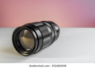 Vintage soviet manual telephoto prime lens with focal length of 200mm close up shot on white and pink background, soft focus