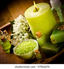 Vintage spa still life with green candle and spring flowers