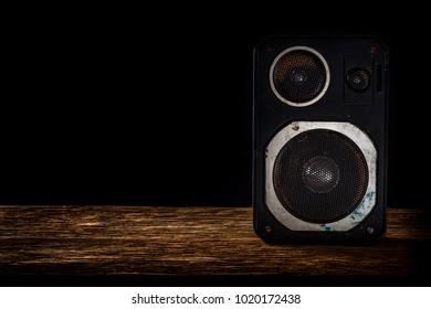 Vintage speaker on wooden table with black background
