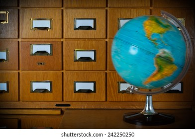 Vintage Spinning Globe in Front of Old Library Card Catalog Stock Photo