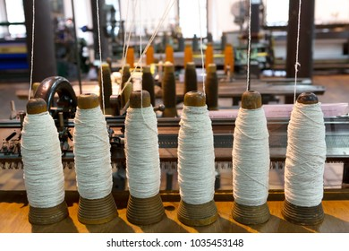 vintage spools of white yarn with old spinning machine