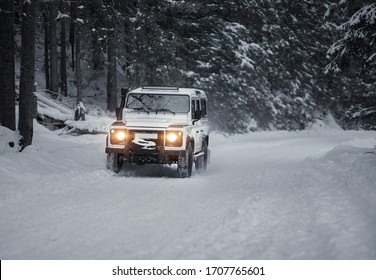 vintage sport utility vehicle driving during snow storm in forest
