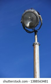 Vintage spotlight outside used for securing a factory or jail perimeter with blue sky background (unedited)