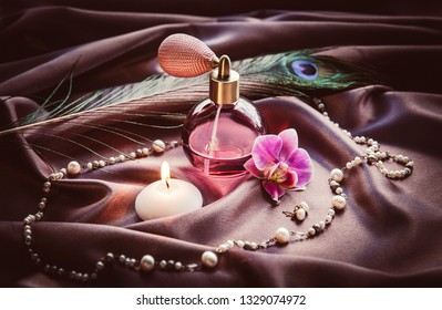Vintage spray atomizer perfume bottle and pearl jewellery on silky dark pink fabric with peacock feather and candle burning, romantic luxurious evening concept.