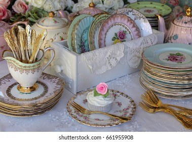 Vintage stacked bone china cake plates in an old drawer with gold cake forks and cupcakes - wedding dessert table