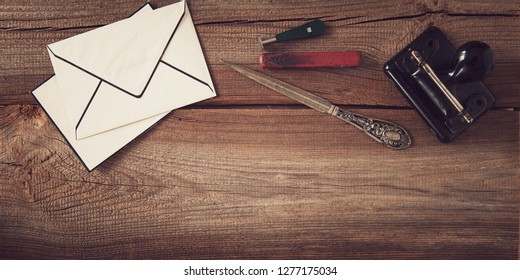 vintage stationery with puncher, paper knife, envelope, seal and sealing wax flat lay on wooden board with copy space