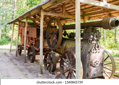 Vintage steam engine for agriculture. Warm bright summer day.