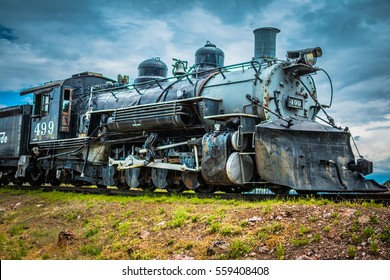 A vintage steam engine with blue cloudy sky and green grassy land in the foreground