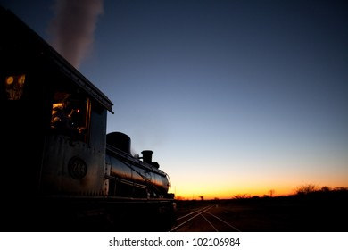 Vintage steam locomotive pointed into the sunset