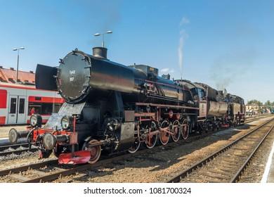 vintage steam train locomotive with smoke on blue sky